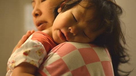 Little Asian girl crying on mother shoulder at night time