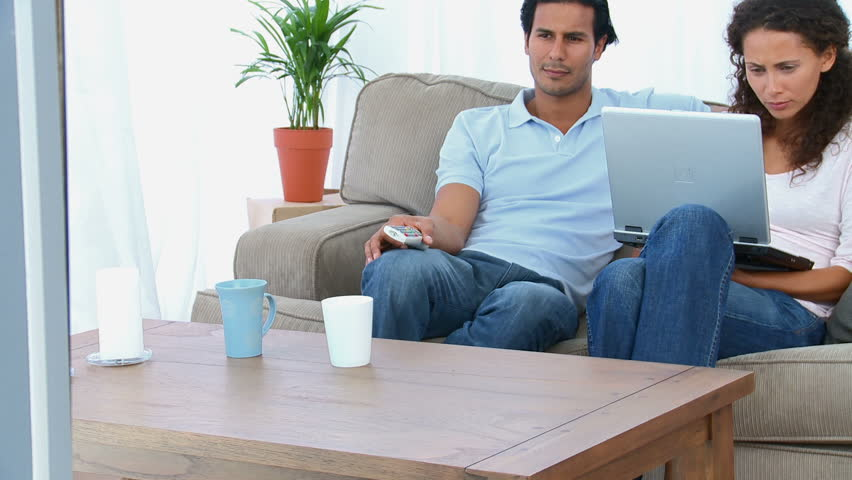 Couple watching a video on the computer sitting on the sofa at home | Shutterstock HD Video #1004872