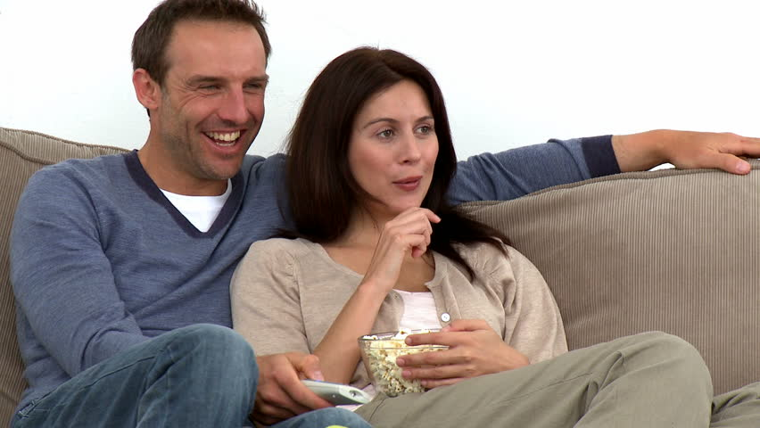 Happy couple watching television with popcorn sitting on the sofa at home