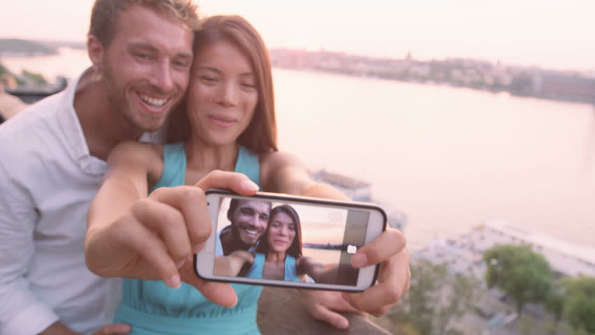 Smart phone selfie - couple taking self portrait using smartphone camera. Dating couple in love having fun taking candid fresh picture photo laughing smiling. Caucasian man, Asian woman at sunset. | Shutterstock HD Video #10063952