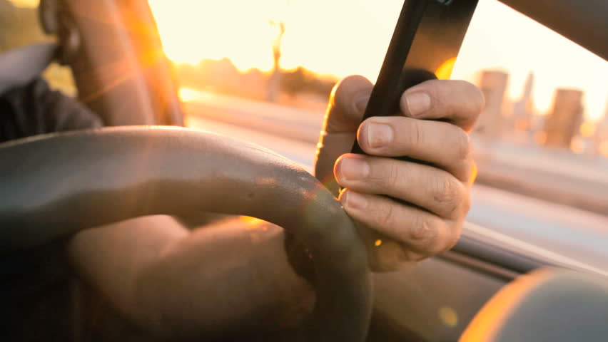 Texting while driving at sunset, distracted driver on cell phone