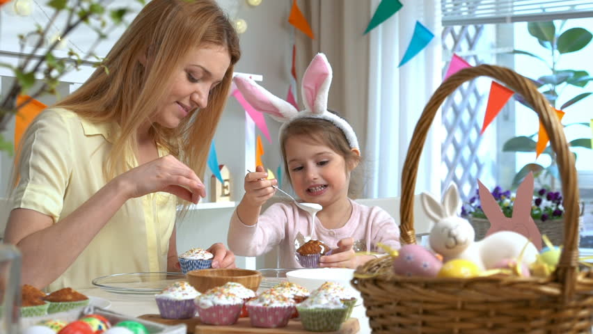 Young mother and her cute little daughter wearing funny rabbit ears are cooking Easter cupcakes sitting at a festive table with basket, eggs and Bunny. Slow Motion | Shutterstock HD Video #1006572352