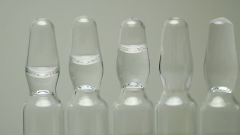 Ampoules with a clear solution for injection stand in a row. panning close-up