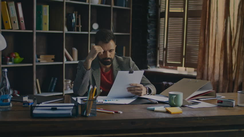 Exhausted man solving business problem. Office worker lies on table. Frustrated business owner. Tired businessman working with documents in office. Serious businessman working on new business project