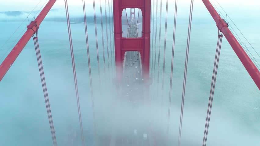 Bird view of the fog going through the famous Golden Gate Bridge. Aerial of the towers of the red bridge with vehicle traffic and yacht going by in the San Francisco Bay on a misty day. California, 4K
