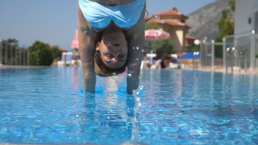 Young beautiful girl jumping in pool. Woman in swimsuit swimming in basin of hotel on sunny day. Summer vacation or holiday concept. Low angle of view Slow motion Close up