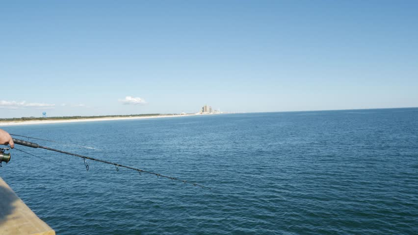 Close up on the hands of a fisherman and his rod and reel as he fishes off a marine pier and reels in his line in a static clip