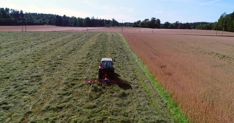 Plowing machine, Cinema 4k aerial view over a plow tractor, harvesting on a grass field, on a sunny autumn day, in Uusimaa, Finland