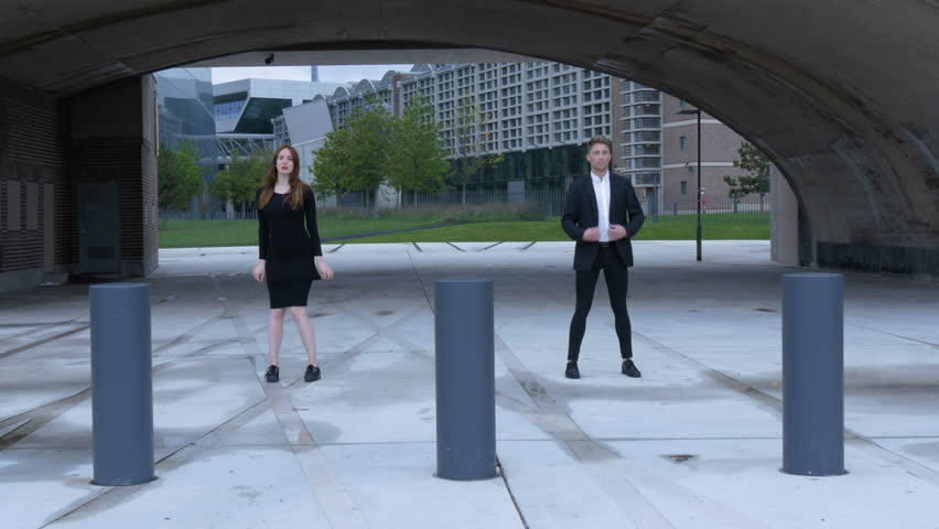 Female and a male dancer walk forward and begin dancing in front of a city bridge and behind bollards. The male dancer is wearing a black suit and the female a black dress.