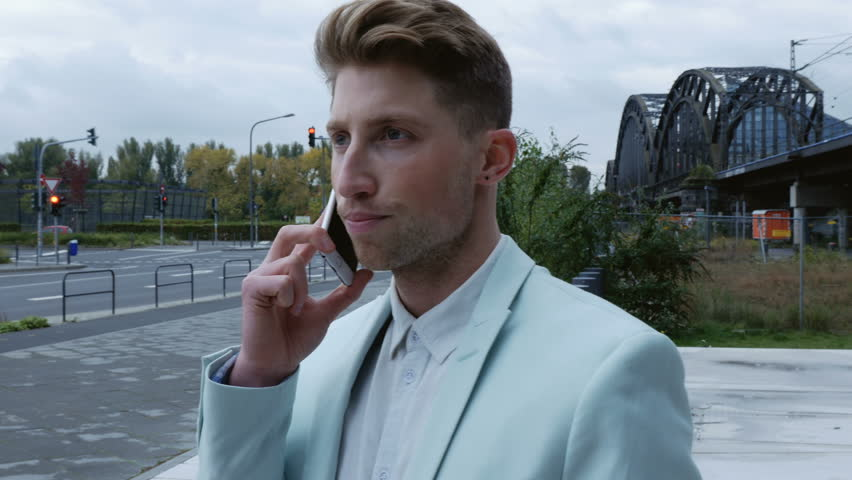 A young man wearing a turquoise tuxedo talking on a mobile phone. A cloudy street scene in the background. Medium close up. Profile.