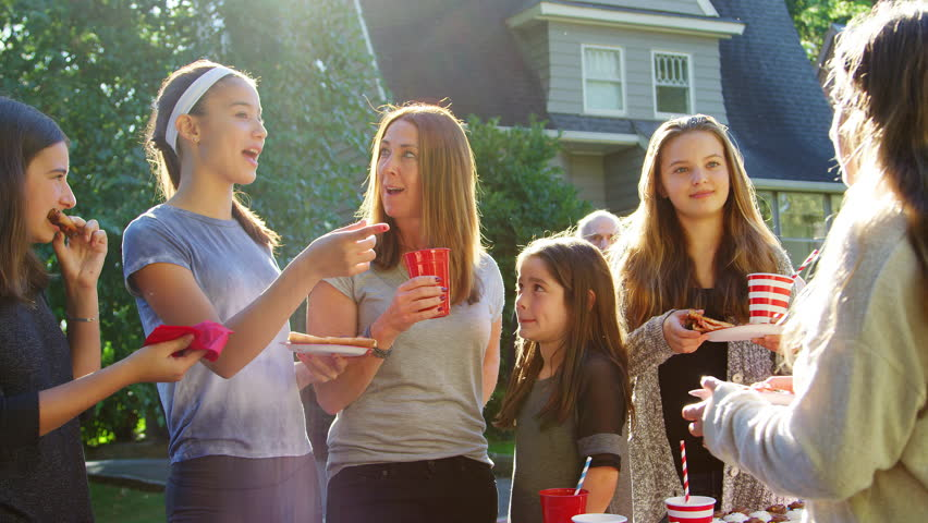 Family and friends talk and eat at a block party