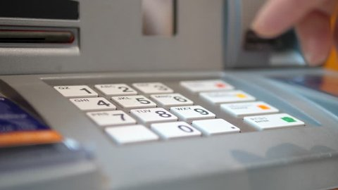 Close Up Hand Entering A Password In ATM Machine From Credit Card
