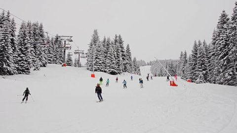 Amateur recreational skiing in mountain ski resort. Ski track and ski lift.
