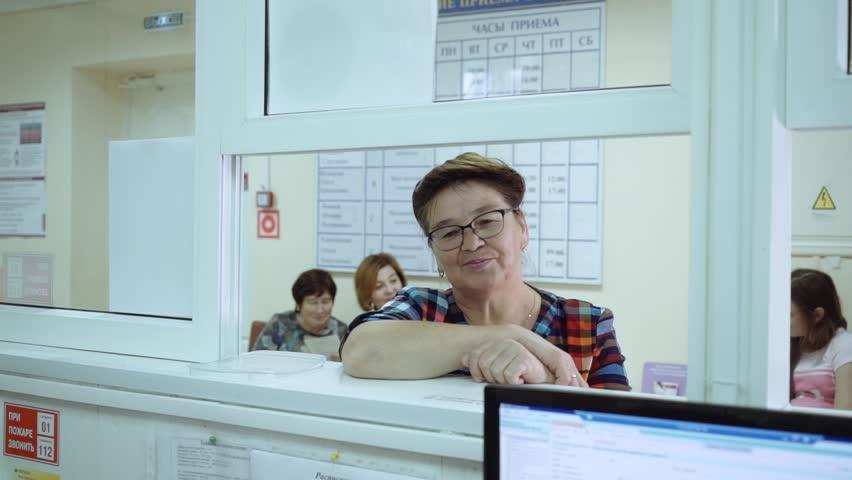 An elderly woman is standing near the hospital registry window.