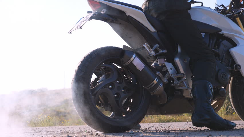 Wheel of sport motorbike starting to spin at asphalt and kicking up pebbles and dirt. Biker performing tire burnout with lots of smoke. Motorcycle starts the movement. Slow motion Close up
