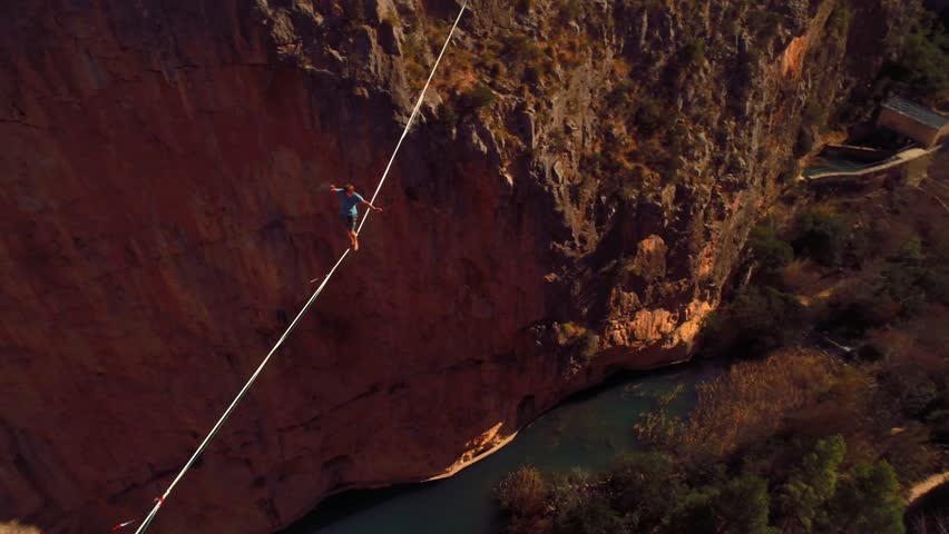 Young Man Slacklining , highlining above a big canyon in Chulilla , Spain . Nature Adventure and leisure sport . Mountain Balance Extreme Hiker Walking Happy, 4k aerial cinematic footage