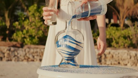 Newlyweds, groom and bride, on a beautiful tropical beach near the ocean. They add white and blue sand to the flask. Festive ceremony with sand. Art of a young couple.