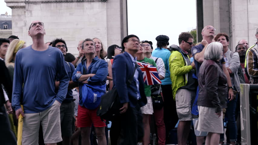 PARIS, FRANCE - JULY 23, 2017:Crowd of people looking up in fascination, watching, pointing - HDR HLG slowmo