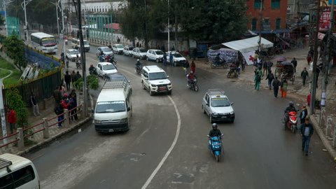 People, cars, motorbikes and rickshaws on the street. The traffic on on the streets in Kathmandu, Nepal. Time-lapse