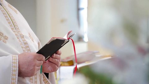 priest reads a bible in church