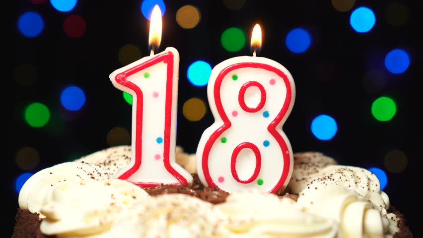 Number 18 on top of cake - eighteen birthday candle burning - blow out at the end. Color blurred background.