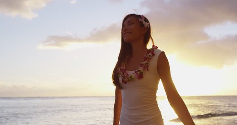 Praising happy freedom woman on beach wearing lei and dress stretching arms up, enjoying sun in worship and meditation zen. Serene girl seen from backside on Hawaii, USA. RED EPIC SLOW MOTION.