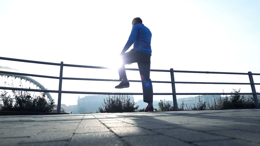 Sportive joggers on bridge in city, man stretching leg, woman running, super slow motion 240fps  #1006910662