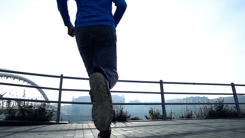 Successful male jogger jumping near river in city, super slow motion 240fps  #1006910692