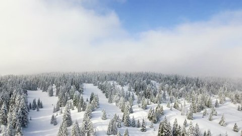 Spectacular drone footage over the high alpine mountains and winter forests of the Col de la Givrine (el. 1228 m.), a high mountain pass in the Jura Mountains, Switzerland.