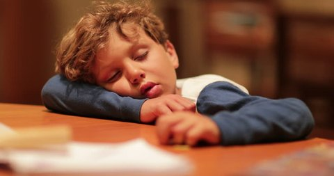 Tired child fell asleep with head on table. Young boy sleeping after a long day. Real life authentic natural shot of sleepy kid