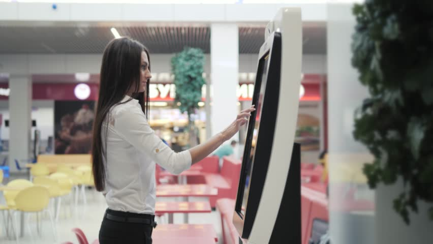 Caucasian female using automated teller machine with big digital screen while standing in shopping mall, woman verifies account balance on banking application via modern device icon