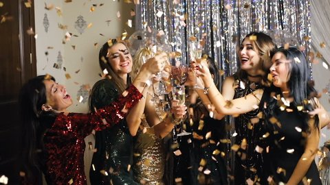 Young woman in glitter dress cheers and drink champagne in flying confetti on New Year party. Super slow motion.