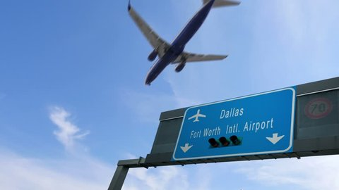 airplane flying over dallas airport signboard