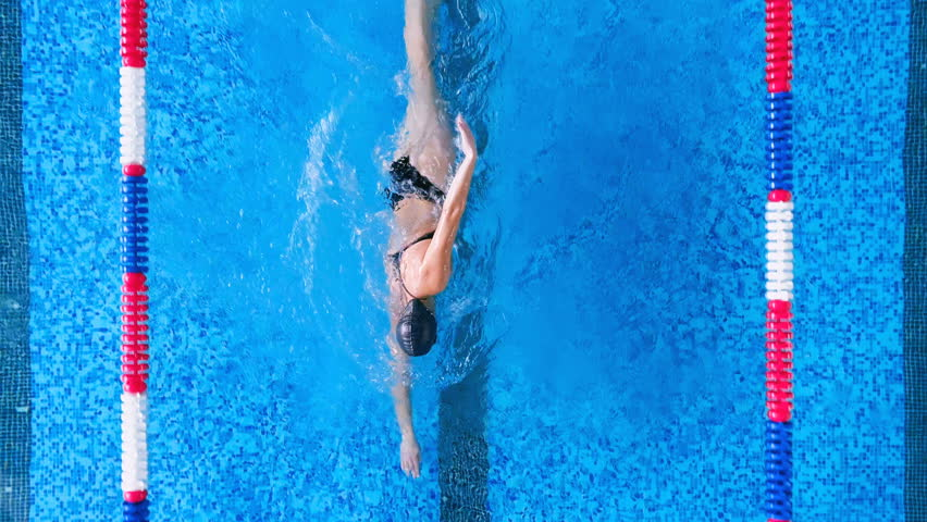 A woman swims in crawl in an open back swimsuit.  | Shutterstock HD Video #1006955692