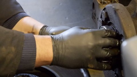 Close up of mechanic's hands working on semi truck diesel engine in repair shop