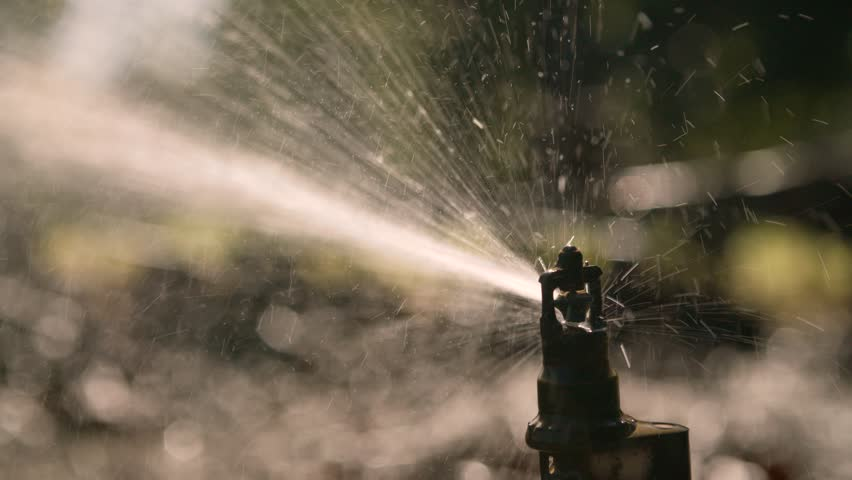 A Sprinkler / Irrigation System Sprays The Farmers Crop, In Slow Motion