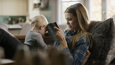 Baby daughter playing with cell phone and mother reading digital tablet / Alpine, Utah, United States