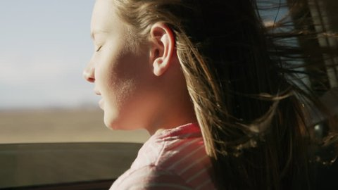 Close up of girl in car leaning out car window enjoying wind blowing hair / Hanksville, Utah, United States