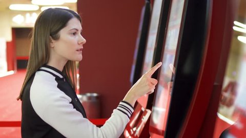 Teenager choosing movie and buying ticket from vending machine at movie theater at mall. Young woman making gestures by touching screen