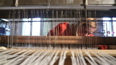 Young woman with down syndrome weaving loom 3/6