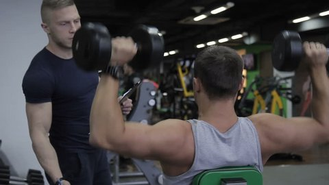 Young sportsman is doing Dumbbell Lateral Raise and his male instructor is writing his results in the gym. The man is sitting on the bench and exercising his pectoralis and the instructor in black