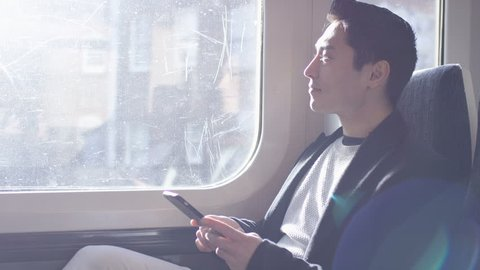 Confident man on a train journey using his phone, in slow motion
