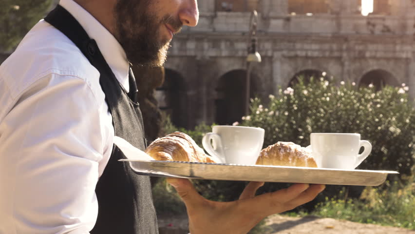 Elegant waiter serving breakfast with breakfast coffee croissant cappuccino on a try outdoor to a bar restaurant table in front of colosseum in rome at sunset | Shutterstock HD Video #1007085622