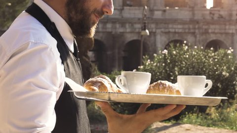 Elegant waiter serving breakfast with breakfast coffee croissant cappuccino on a try outdoor to a bar restaurant table in front of colosseum in rome at sunset