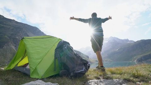 Young man on a hike stands by his tent near stunning mountain lake arms outstretched. Male hiker arms wide open in nature surrounded by scenic mountain lake landscape. Success at mountain top