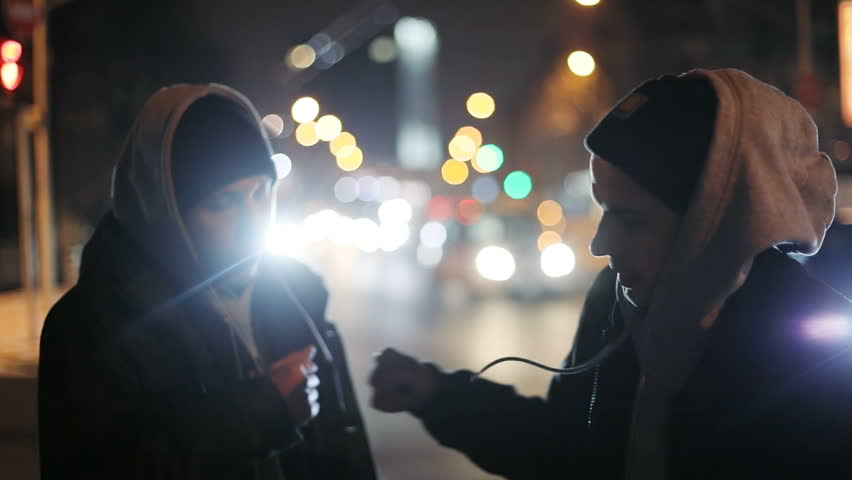 young men man male friends meeting pound hugging each other shaking hands greeting greet outside night city light cars traffic background bokeh urban friendship cool guys gesturing shake confident