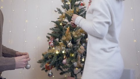 Japanese couple putting decorations on their chirstmas tree.