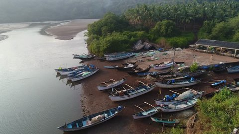 A small parking lot for a lot of fishing boats. Several coloured wooden boats and dinghys stand on the shore in anglers village in Goa, India. Aerial view.