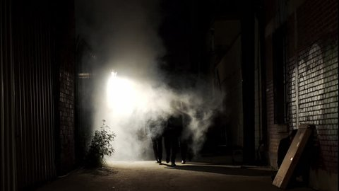 Wide shot of a silhouetted group of three men walking down a dark alley at night, passing through a backlit cloud of steam.
