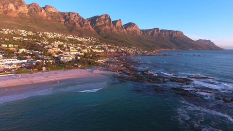 Aerial view of Camps Bay, Cape Town in South Africa at sunset with the ocean, beach, tourists and mountains.